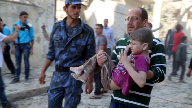 A man holds an injured boy after what activists said was a barrel bomb dropped by forces loyal to Syria's President Bashar al-Assad hit a school and a residential building in Seif al-Dawla neighborhood of Aleppo on May 3.