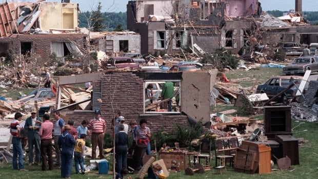 With damaged houses all around them, neighbours, volunteers and friends take time out for lunch on June 2, 1985, during a cleanup effort following a tornado in Barrie, Ont. Environment Canada meteorologist Geoff Coulson says the province is overdue for another major tornado.