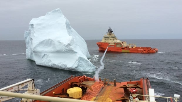 The photo captures the moments after a rope line was shot between two vessels so they could move in tandem to guide the iceberg away.