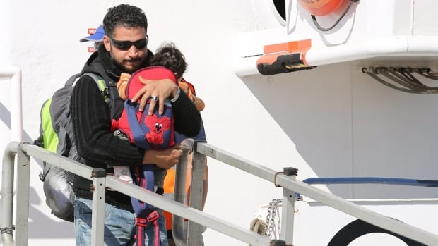 A migrant carries a baby as he disembarks from the Migrant Offshore Aid Station vessel Phoenix in the harbour of Augusta, Italy. Southern EU states are clamouring for EU help to deal with thousands of migrants reaching Europe by boat from Libya.