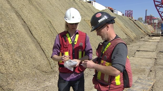 Ryan Eldridge and Gareth Spicer,  archeologists with Turtle Island Cultural Resource Management, examine items they discovered during excavation for the Walterdale Bridge.