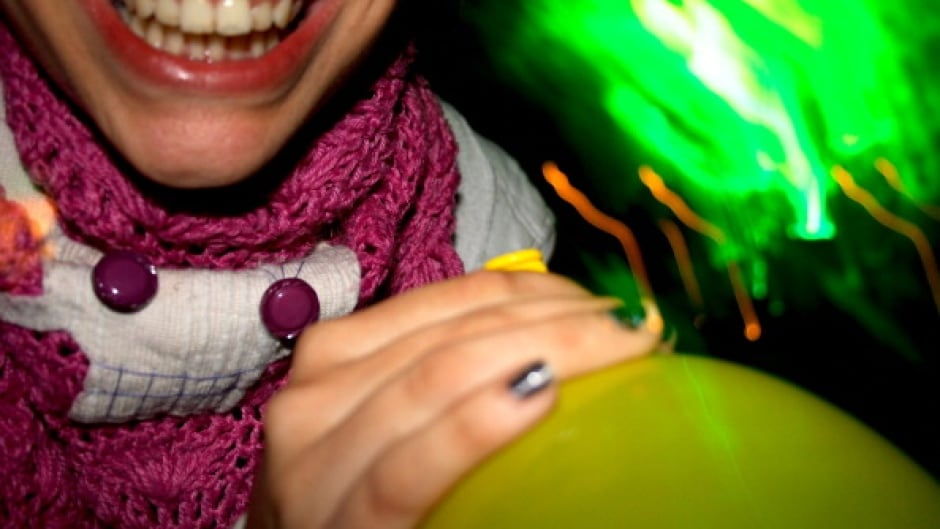 Detail of someone smiling and holding a laughing gas balloon. (Photo by Universal Images Group via Getty Images)