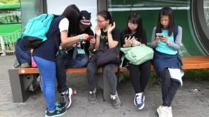 South Korean middle school students use their smartphones at a bus station in Seoul, South Korea. Security researchers say they found critical weaknesses in a South Korean government-mandated child surveillance app.