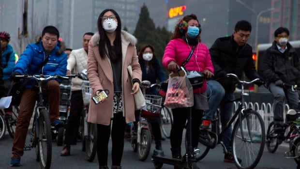 Pedestrians and cyclists in China wear mask against heavy pollution in Beijing. The IMF estimates China is subsidizing fossil fuels $2.3 trillion a year by failing to account for health and pollution effects.