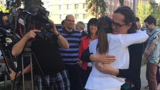Transgender activist Marni Panas embraces the mother of a seven-year-old transgender child who has won access to the girls washroom at her Catholic school in Edmonton.