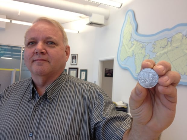 Gary McLeod, chief electoral officer, with tiebreaker coin
