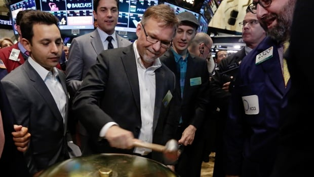 Shopify CFO Russ Jones, centre, rings a ceremonial bell as the Canadian company's IPO begins trading on the floor of the New York Stock Exchange on Thursday. He is joined by CEO Tobias Lütke, right, in hat, and NYSE President Tom Farley, second left.