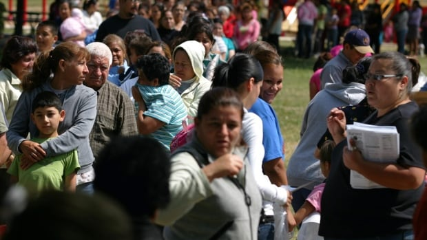 Migrant workers line up at the U.S. border to apply for farm work. Two temporary foreign workers who were sexually harassed at an Ontario fish-processing plant have been awarded a total of $200,000.
