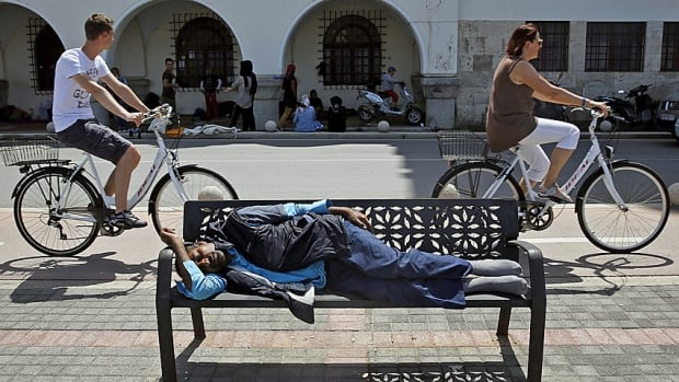 An Afghan immigrant sleeps on a bench outside a local police station on the Greek island of Kos last week as tourists bike by. Hundreds of immigrants and Syrian refugees arrived on the tourist island over the past three days.