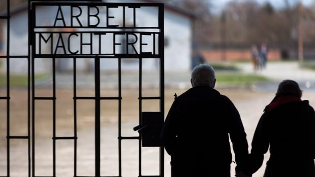 Documents reveal 133 alleged and suspected Nazis were paid $20.2 million in U.S. Social Security benefits. In this 2012 photo, a couple walks past the slogan 'Arbeit Macht Frei' (Work Sets You Free) at the main entrance of the Sachsenhausen Nazi concentration camp on the international Holocaust remembrance day in Oranienburg, Germany.