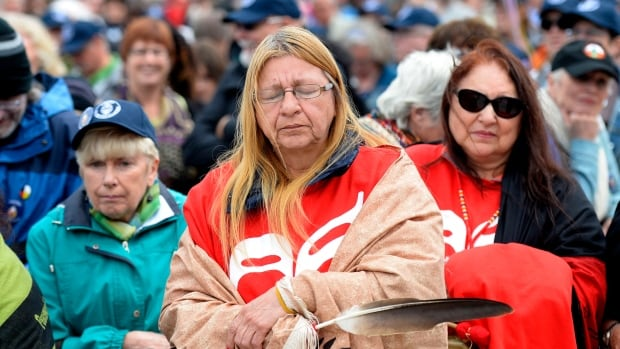Debbie Stephens holds an eagle feather as she pauses before the start of the walk for reconciliation, part of the closing events of the Truth and Reconciliation Commission on Sunday in Gatineau, Que.