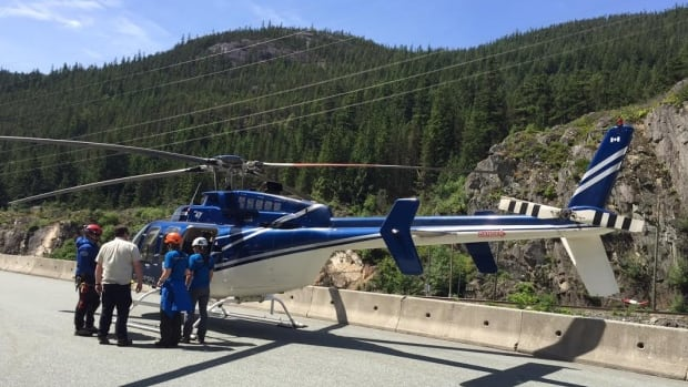 A helicopter lands on the Sea-to-Sky Highway Sunday morning during a rescue operation for a hiker who fell 9 metres onto a ledge while scaling a rockface in the Cheakamus Canyon.