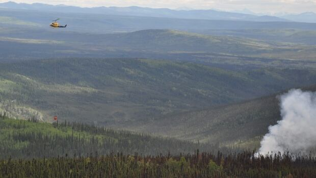 A helicopter helps contain a 220-hectare fire 11 km northeast of Dawson City, Yukon.