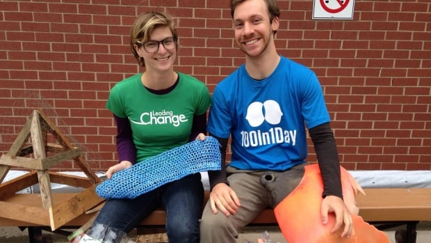 Organizers Anika Riopel and Cameron Christensen of the Wave of Waste project pose with some marine garbage they collected.
