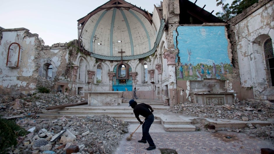 A man sweeps out the earthquake-damaged Santa Ana Catholic church, on Jan. 12, 2013 - three years after the disaster.