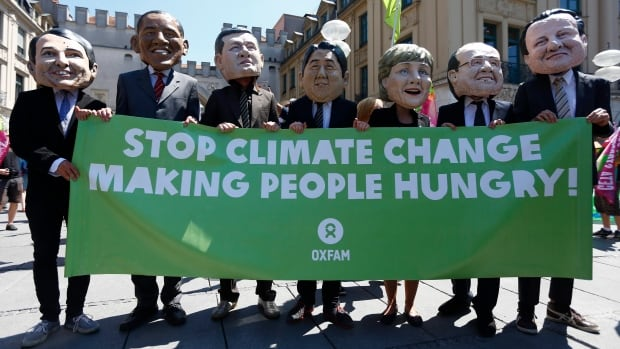 Demonstrators with masks depicting the G7 leaders hold a poster warning of climate change during a protest against the upcoming G7 summit in Munich. The summit will take place next week.