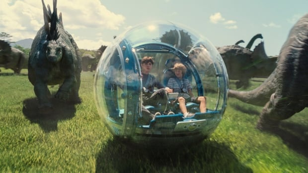 Actors Nick Robinson and Ty Simpkins interact with some of Jurassic World's herbivorous dinosaurs in a scene from the latest of Steven Spielberg's groundbreaking Jurassic Park series.