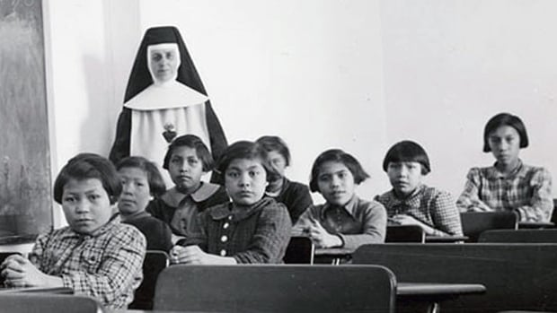 Female students and a nun pose in a classroom at Cross Lake Indian Residential School in Cross Lake, Manitoba in a February 1940 archive photo.