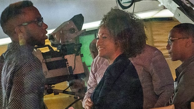 """Washington State civil rights advocate Rachel Dolezal talks with family member Izaiah Dolezal (L) while her son Franklin looks on, Tuesday. Accused of """"racial appropriation,"""" Dolezal told interviewers she has identified as black since she was a child."""