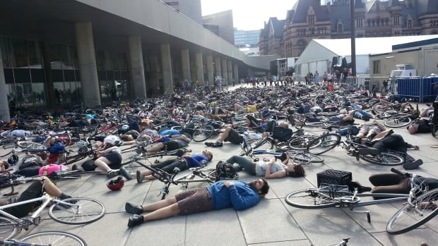 Hundreds lie on the ground for a cyclist 'die-in'.