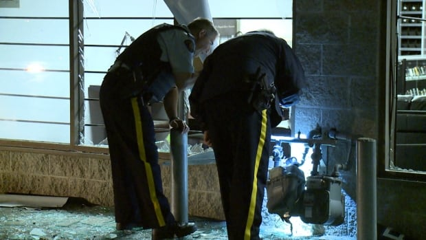 Members of Langley RCMP take a close look at the damaged gas meter in front on All Day Vapes, after a suspicious explosion Friday night.