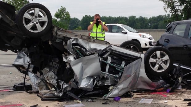 An SQ investigator takes photos of a Longueuil car crash in June 2015.