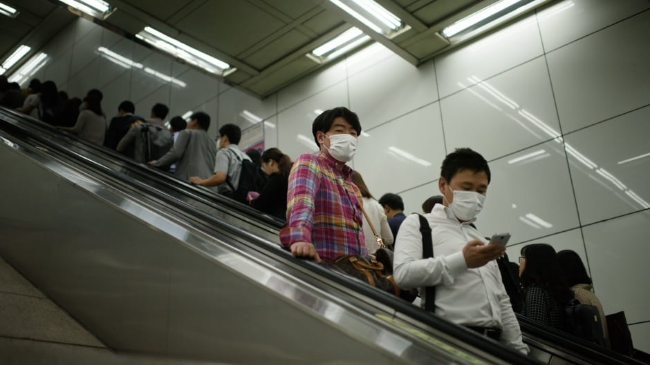 Commuters wearing face masks ride an escalator in a subway in central Seoul,  South Korea on June 5, 2015.