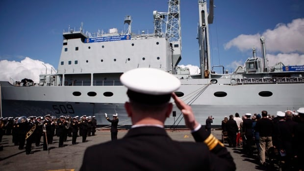 Naval officers are seen at CFB Esquimalt for HMCS Protecteur's paying-off ceremony in Esquimalt, B.C., on May 14. CBC News has learned the Liberal government is delaying approval of a deal to convert a civilian cargo ship into a military supply vessel.