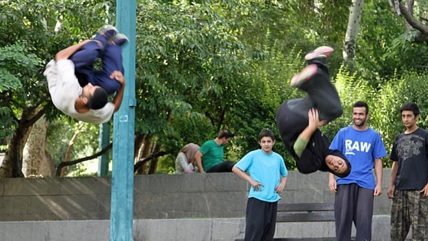 25-year-old Nilofar Moghadam and teammate Milad Yazandoost, 22, practice the urban sport of parkour, a combination of acrobatics and obstacle courses, in a park in Tehran.