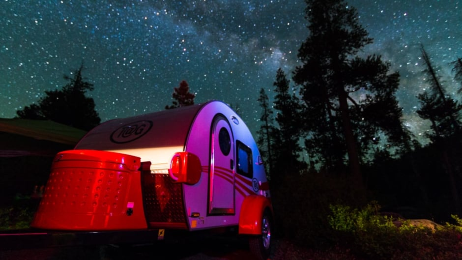 A chic teardrop camper sits under the light of the Milky Way at Kirkwood Lake in California.