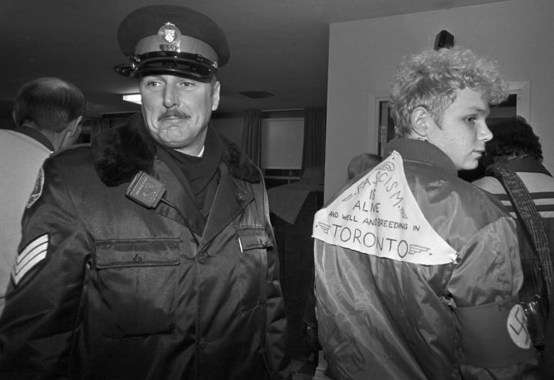 A member of the gay community wearing a swastika and a sign stating  'Fascism is alive and well and breeding in Toronto' walks past a police  officer as he ...
