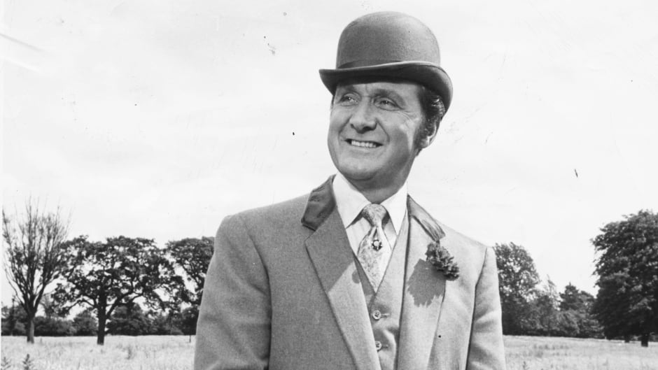 Portrait of actor Patrick Macnee, standing in a field, wearing a bowler hat and suit, March 5,1969.