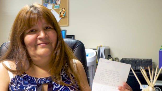 Claudette Okemow holds up a handwritten thank-you card from one of the mothers who went through the CLOUT program.