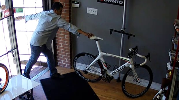In this surveillance image released by Evolution Cycles, which has been viewed thousands of times on the shop's Facebook page, a man begins to wheel away the high-end Cipollini road bike.