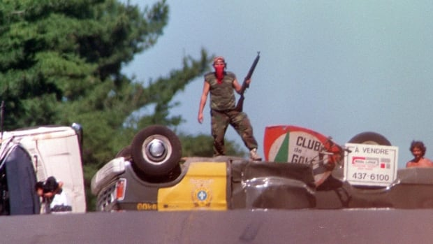 An armed warrior towers over a overturned police vehicle blocking Highway 344 through the Mohawk community of Kanesatake near Oka, Que. on July 11, 1990 after a police assault to remove Mohawk barriers failed.
