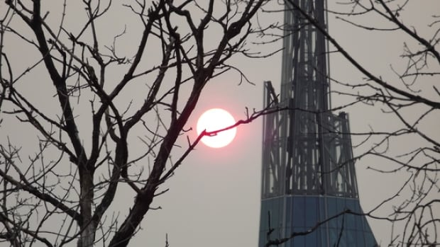 The sun sets beside the Tower of Hope atop the Canadian Museum for Human Rights.
