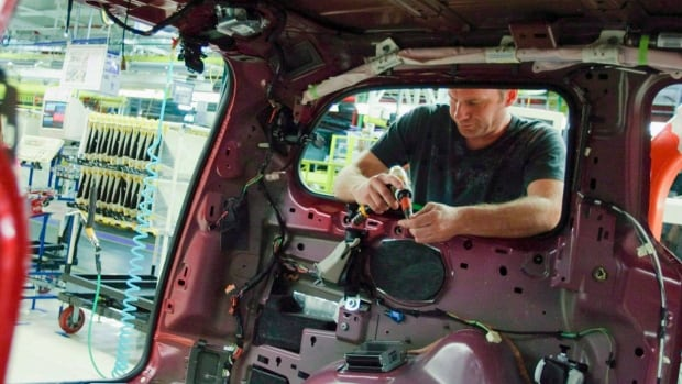 An auto worker assembles a car at a Canadian auto plant. Sales of cars and car parts were one of the few bright spots in April as retail sales and the overall economy shrank.