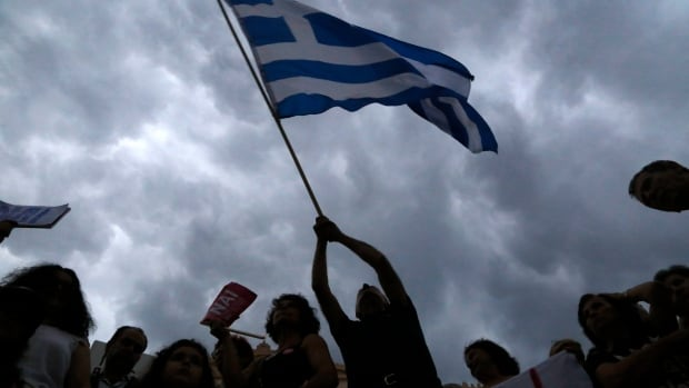 A demonstrator waves a Greek flag during a rally organized by supporters of the Yes vote to the upcoming referendum, in Athens, on Tuesday evening.