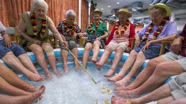 Residents of a retirement home refresh their feet in a pool on a hot summer day in Belgium last summer. Health Canada said the elderly are among those who are most at risk for heat-related illness or death.