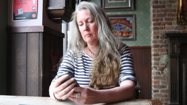 Nicola Brookes checks her mobile device for messages. She has dealt with online harassment for five years and is still fighting to have her trolls prosecuted for their alleged crimes.