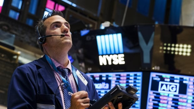 A trader looks at boards shortly after the closing bell Wednesday. The New York Stock Exchange, a unit of Intercontinental Exchange Inc, reopened at 3:10 p.m. ET after being halted shortly after 11:30 a.m.