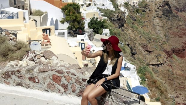 A tourist takes a selfie in the village of Oia on the Greek island of Santorini, Greece, July 1.