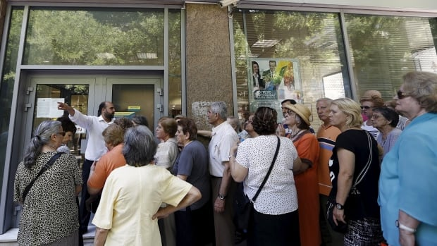 A bank manager points as pensioners wait in front of a National Bank branch to receive part of their pensions at an Athens neighbourhood. A new proposal from Greece has been submitted to creditors, but bank woes are expected to continue in the days ahead.