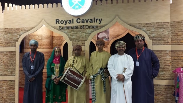 The Royal Cavalry of Oman has set up their booth in the Agrium Western Event Centre at the Calgary Stampede where they greet visitors in traditional Omani clothes .