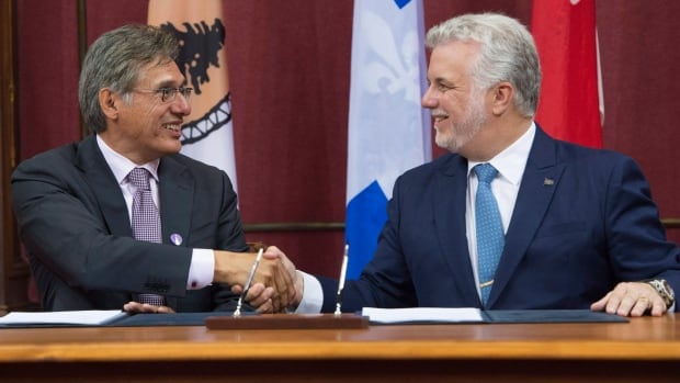 Matthew Coon Come, grand chief of the Grand Council of the Crees, left, shakes hands with Quebec Premier Philippe Couillard after they signed an agreement on forestry on Monday at the legislature in Quebec City.