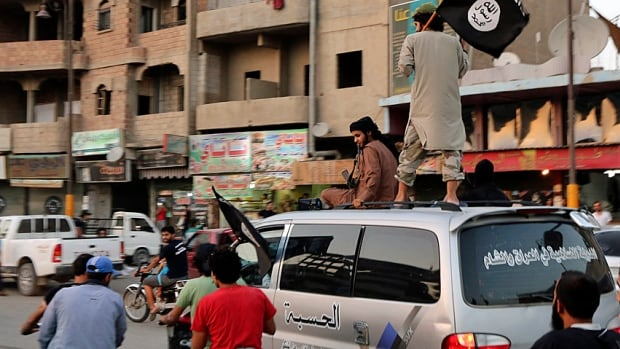 ISIS supporters wave the group's flags as they drive around Al-Raqqa in north-central Syria in June 2014.