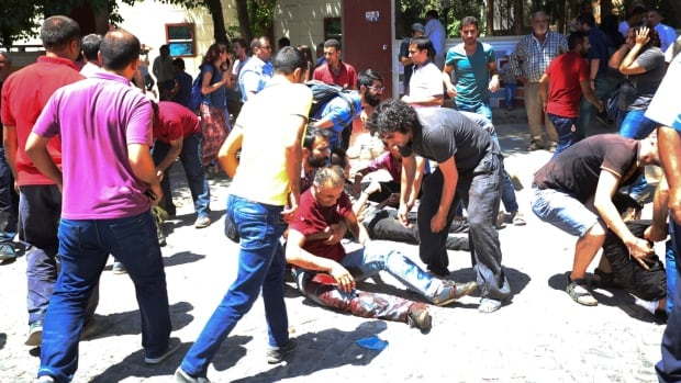 People help the wounded after an explosion in the southeastern Turkish city of Suruc near the Syrian border, on Monday.