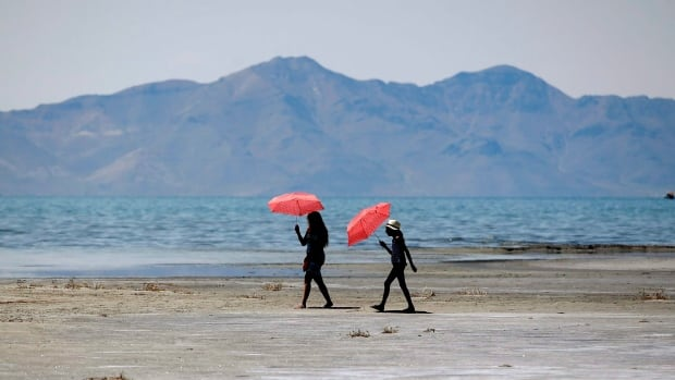 Renee Jaime, 12, and her aunt, Sandra Jaime, of Mexico, shield themselves from the sun as they visit the Great Salt Lake, near Salt Lake City, which saw record temperatures in June. Globally, the first six months of 2015 were one-sixth of a degree warmer than the previous record, set in 2010, averaging 14.35 Celsius (57.83 degrees Fahrenheit).