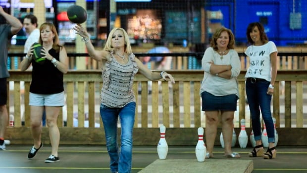 Stacy Wesley throws a football during a round of fowling, a sport created by Detroit area resident Chris Hutt by combining football and bowling.