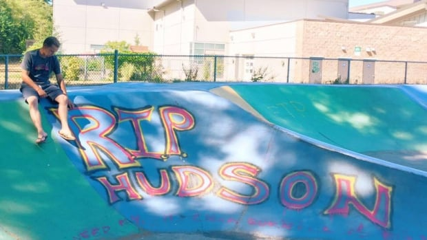 Beaudry Brooks sits next to a spray painted tribute to his brother Hudson Brooks.